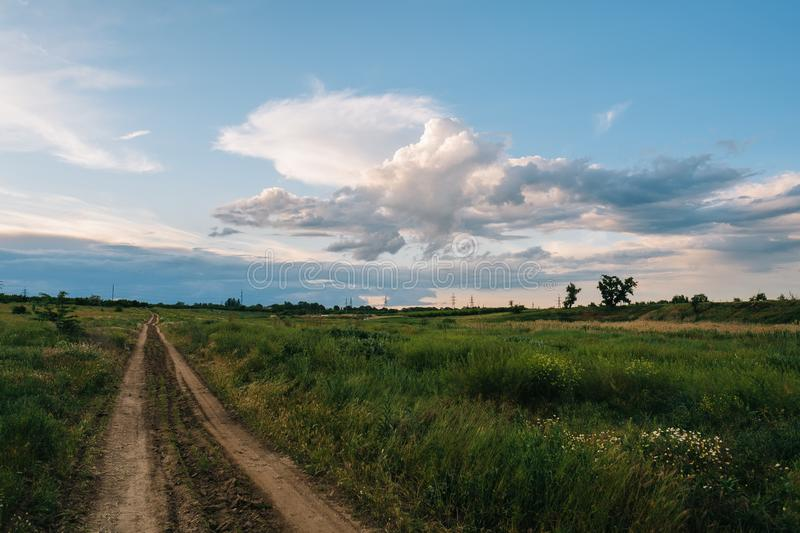 Country road with grass, trees and clouds at evening stock image