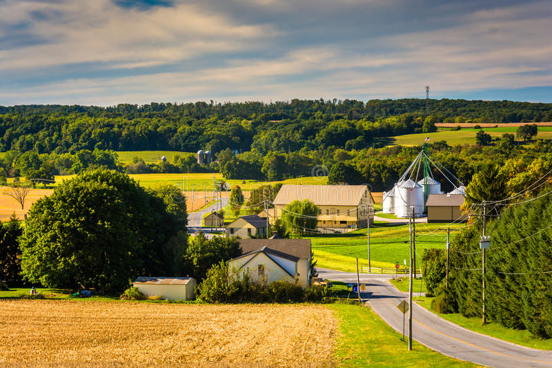 Country road and view of silo and barn on a farm in rural York C royalty free stock images