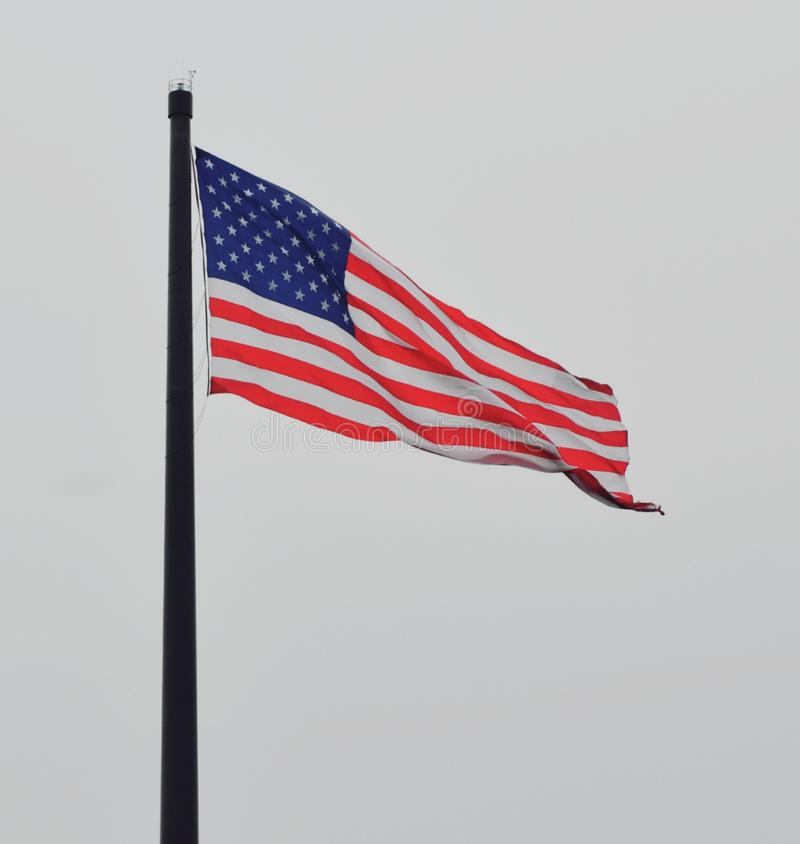 American Flag Flying high on cloudy afternoon. Big United states of America flag. In Sheboygan Wisconsin royalty free stock image