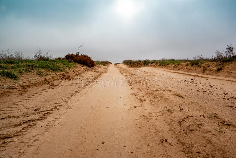 Country sandy road through the desert fields. In cloudy day royalty free stock images
