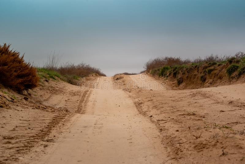 Country sandy road through the dessert fields. In the cloudy winter day royalty free stock image