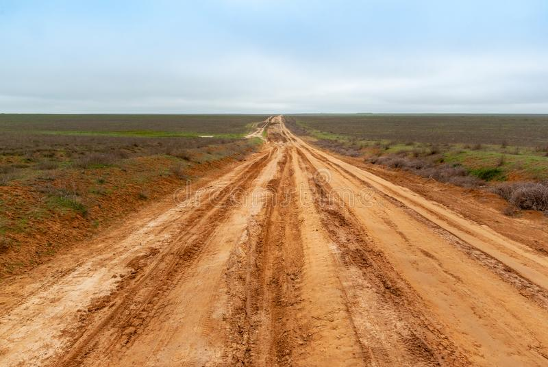 Country sandy road through the flat semidesert fields. In the cloud day stock image
