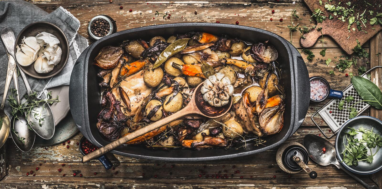 Country stew in vintage casserole with cooking spoon and roasted vegetables on rustic kitchen table background with tools stock photography