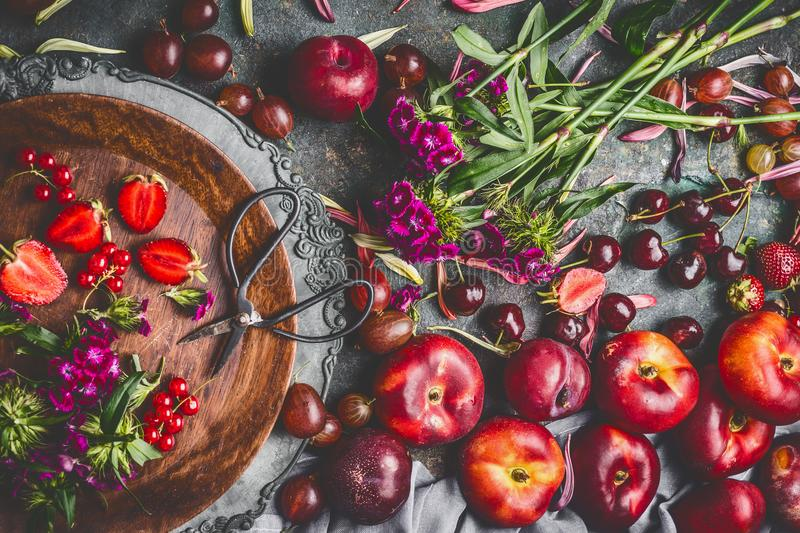 Country still life with various summer seasonal fruits and berries with garden flowers in plate on dark rustic background. Top view royalty free stock photo