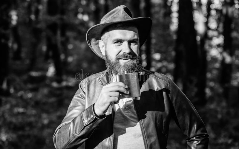 Country style. Bearded man in cowboy hat walk in park outdoor. man hipster relax in autumn forest. Spring weather royalty free stock photo