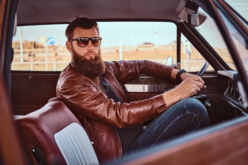 Bearded male in sunglasses dressed in brown leather jacket driving a retro car. Country style concept. Bearded male in sunglasses dressed in brown leather royalty free stock image