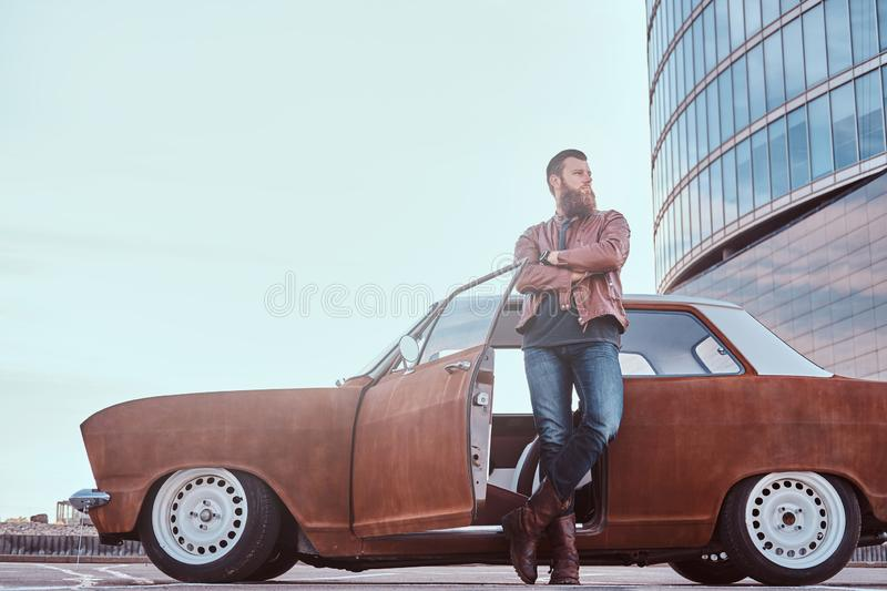 Stylish bearded male in old-fashioned clothes leaning on a tuned old retro car with open door in the city parking near stock images