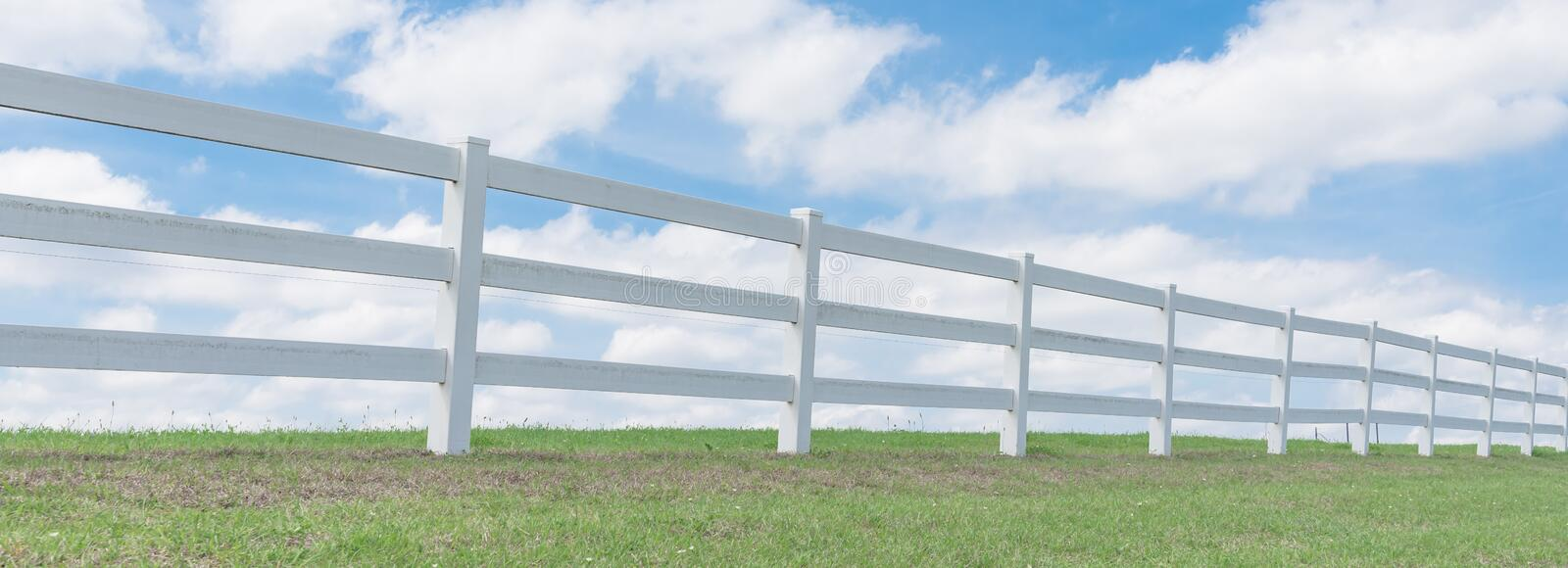 Country style wooden fence against cloud blue sky. Panorama white country style wooden fence against cloud blue sky. White fences on green grass at farm ranch royalty free stock photo