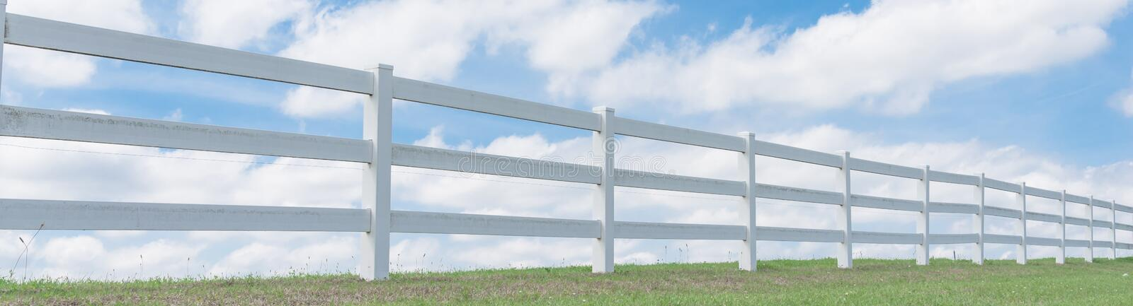 Country style wooden fence against cloud blue sky. Panorama white country style wooden fence against cloud blue sky. White fences on green grass at farm ranch stock image