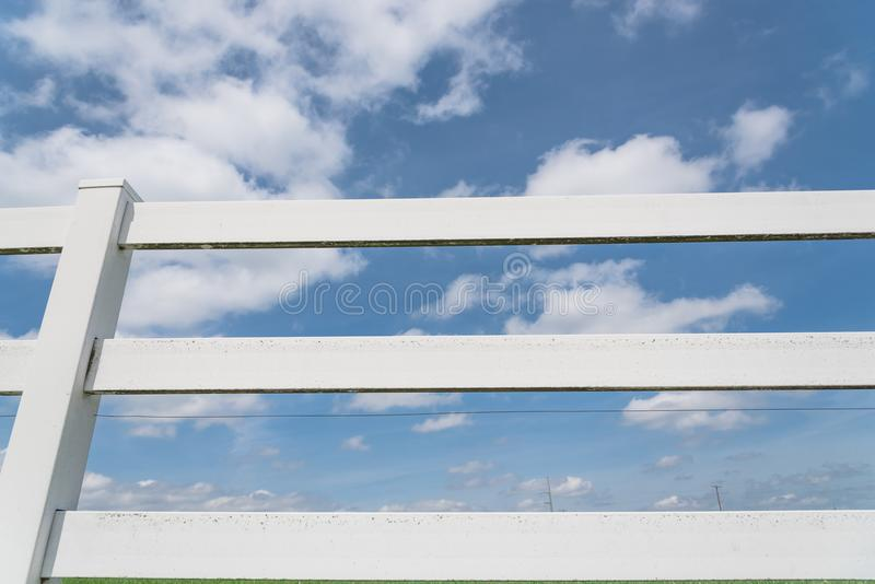 Country style wooden fence against cloud blue sky. White country style wooden fence against cloud blue sky. White fences on green grass at farm ranch land field royalty free stock images