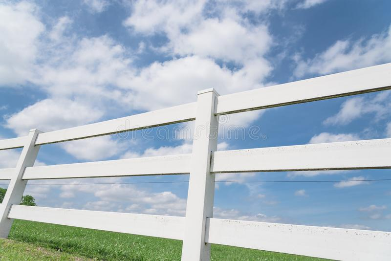 Country style wooden fence against cloud blue sky. White country style wooden fence against cloud blue sky. White fences on green grass at farm ranch land field royalty free stock image