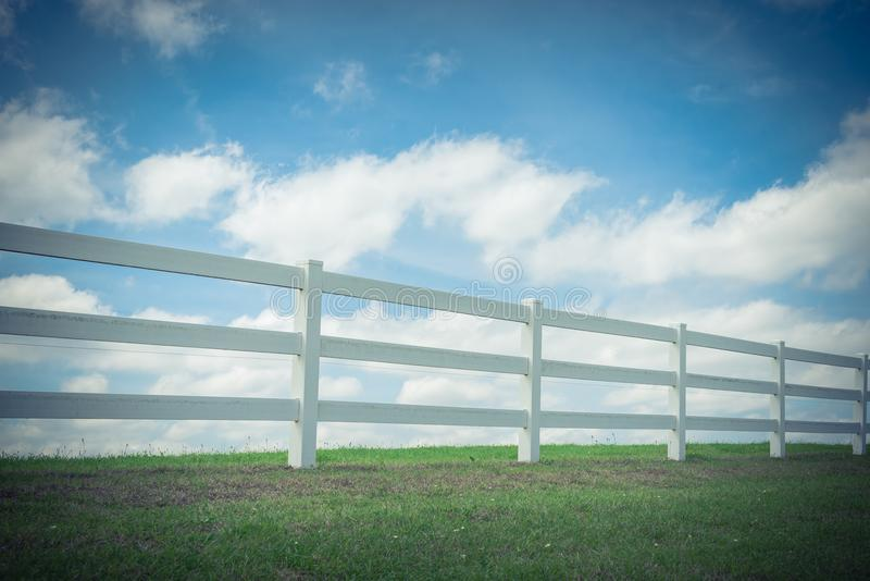 Country style wooden fence against cloud blue sky. White country style wooden fence against cloud blue sky. White fences on green grass at farm ranch land field stock photos