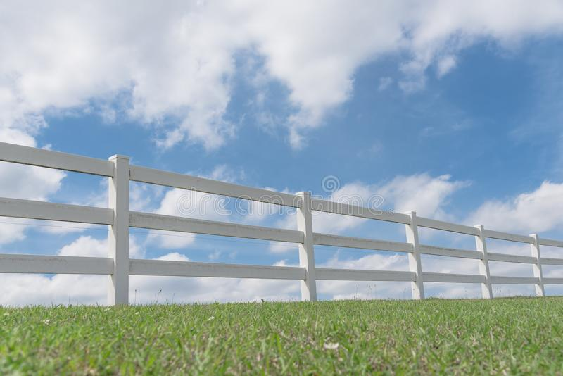 Country style wooden fence against cloud blue sky. White country style wooden fence against cloud blue sky. White fences on green grass at farm ranch land field royalty free stock photos