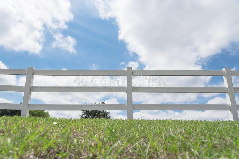 Country style wooden fence against cloud blue sky. White country style wooden fence against cloud blue sky. White fences on green grass at farm ranch land field stock images