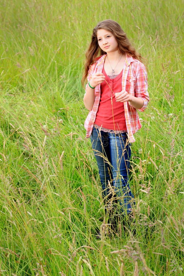 Country Teen Daydreaming. A pretty teenage girl with long brown hair standing in a field of tall grass wearing a red plaid shirt gazing off daydreaming. Shallow stock photo