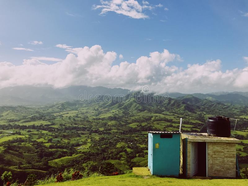 Country toilet and bathroom on mountain Redonda. Against green Dominican mountains an cloudy sky. Sun is harsh but sky has some huge clouds. Toiled is colored royalty free stock images