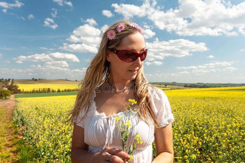 Country woman standing near fields of canola and wheat royalty free stock image