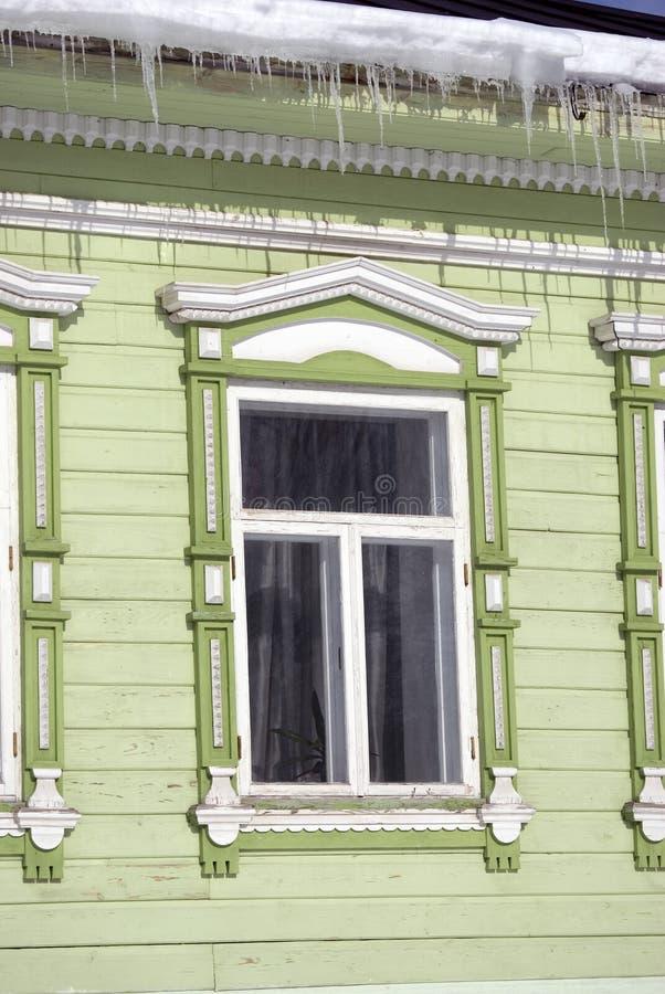 Countryhouse, fachada e janela de madeira verdes Os sincelos cobrem o telhado fotos de stock royalty free