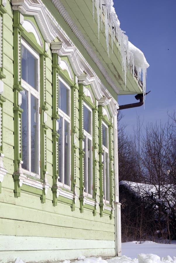 Countryhouse, fachada e janela de madeira verdes Os sincelos cobrem o telhado fotos de stock