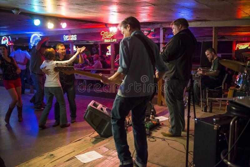 Countrymusikmusikbandspela och folk som dansar i den brutna ekerdansstället i Austin, Texas royaltyfri foto