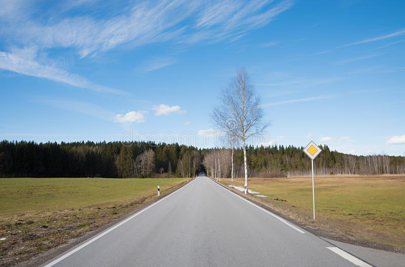 Countryroad directement à la forêt, avec le poteau de signalisation images libres de droits
