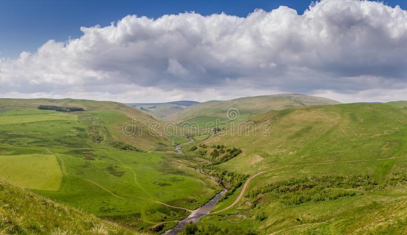 The countryside of Alwinton, Northumberland. The beautiful countryside of Alwinton, Northumberland under a blue sky with fluffy white clouds stock photo