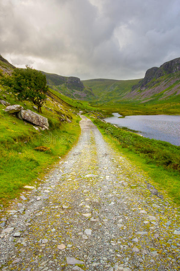 Countryside on Dingle Peninsula. Beautiful valley on Dingle Peninsula with country road, lake and mountains stock images