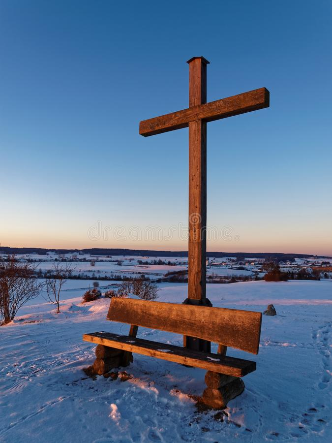 Countryside landmark in snowy winter scenery by sunset. Simple wooden landmark by sunset in the snow-covered German countryside. Traces in the snow lead to the royalty free stock photo