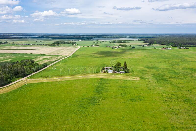 Countryside landscape with farm and cultivated fields under blue sky. aerial view stock image