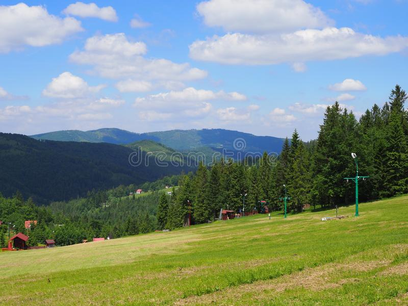 Countryside landscape of grassy field and forest at Beskid Mountains range on Bialy Krzyz in POLAND royalty free stock photography