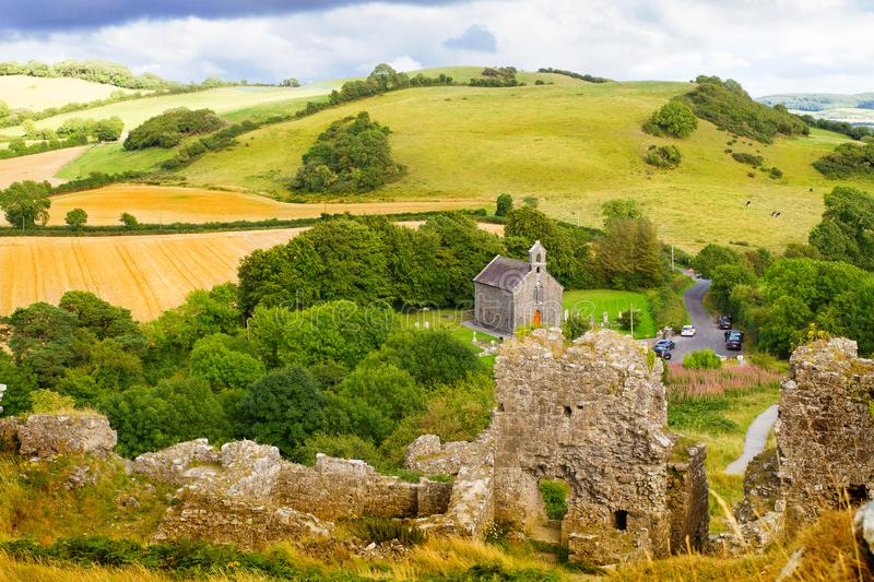 Countryside landscape with ruined castle, hills, forest, meadows and sky royalty free stock images