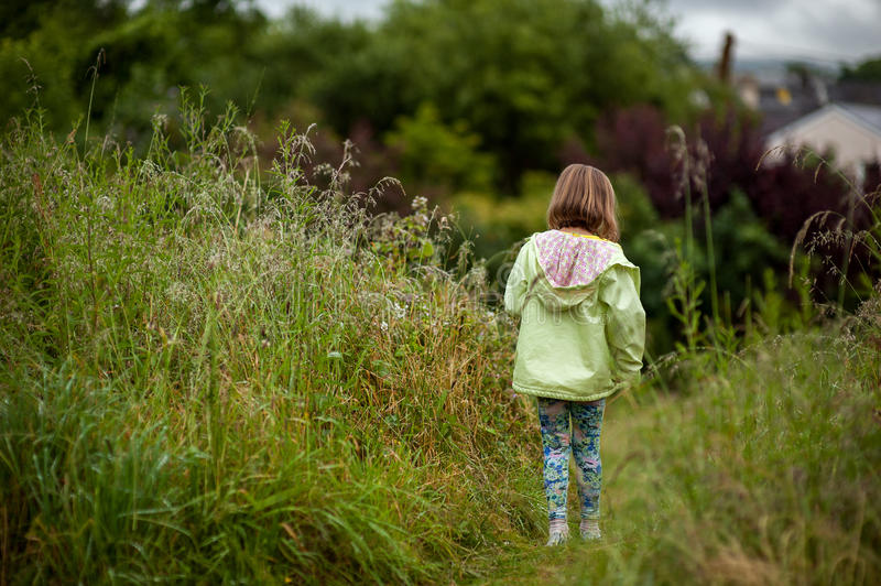 In the Countryside. A little girl walking through a field of tall grass royalty free stock images