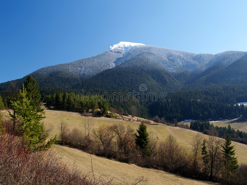 Countryside and mountains. Scenic view of fields and mountains in countryside with snow capped mountain in background royalty free stock photos
