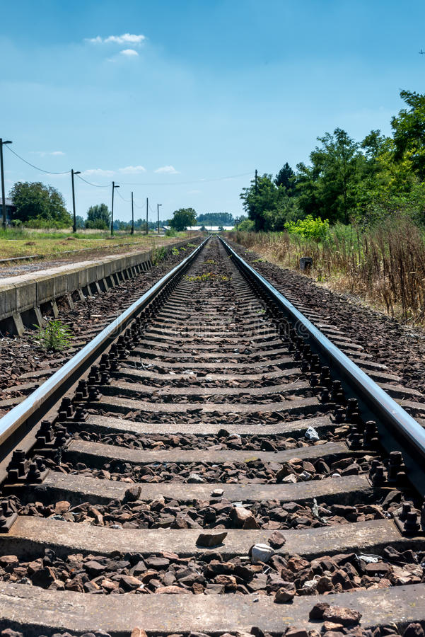 Countryside railroad track in station with platform stock photo