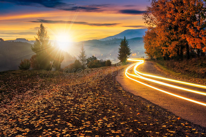 Countryside road with car lights at sunset royalty free stock photo