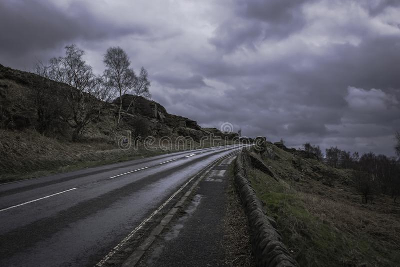 Countryside road with stone walls aside in Peak District National Park,Derbyshire,Uk.Cloudy sky and scenic panorama in background. British landscape in spring stock photo