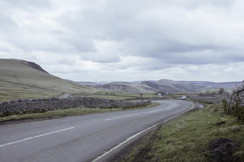 Countryside road with stone walls aside in Peak District National Park,Derbyshire,Uk.Cloudy sky and scenic panorama in background stock images