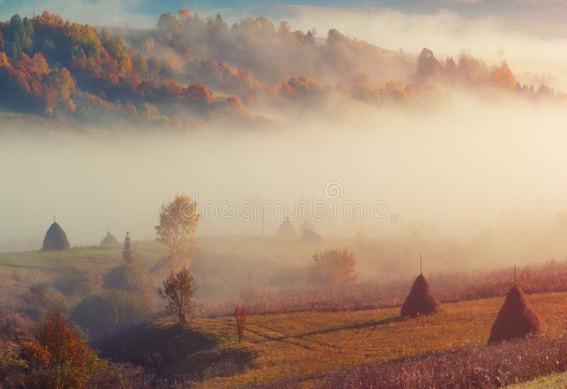 Countryside rural mountain hill landscape with haystack and morning fog. stock images