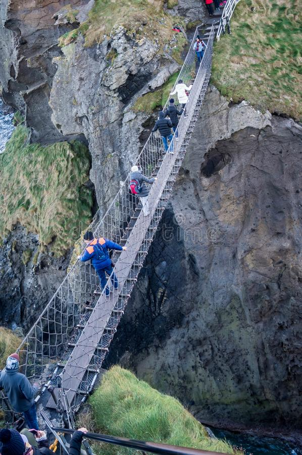 Group of tourists crossing the famous rope bridge on the north coast of Northern stock image