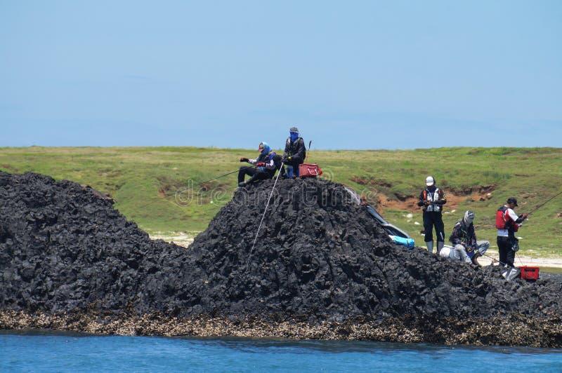 CountyPescadores Penghu, Тайвань - рыба группы людей на прибрежном рифе трясет стоковое изображение rf