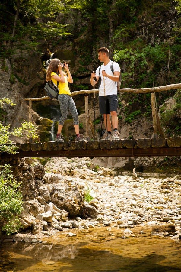 Couole novo ativo que caminha na natureza que descansa perto do waterfalll e imagem de stock royalty free