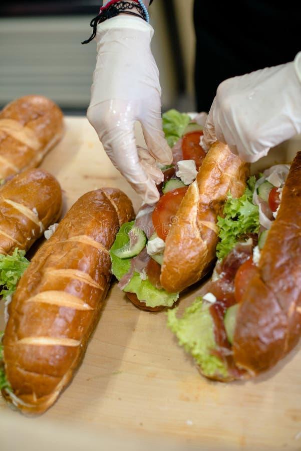 Coupé de l'homme préparant des sandwichs image stock