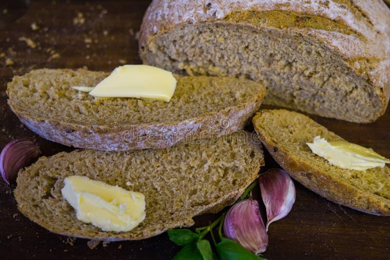 A coupé en tranches le pain frais avec des tranches de clous de girofle de beurre et d'ail images libres de droits