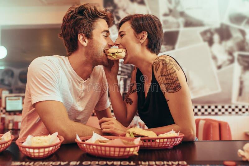 Coupé in romantische stemming die een hamburger delen bij een restaurant stock afbeelding