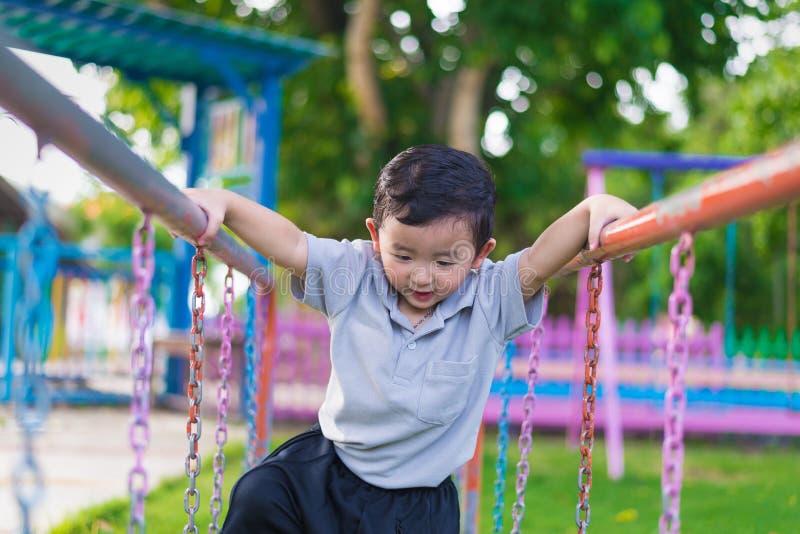 Coup asiatique de garçon la barre en métal au terrain de jeu extérieur photographie stock libre de droits