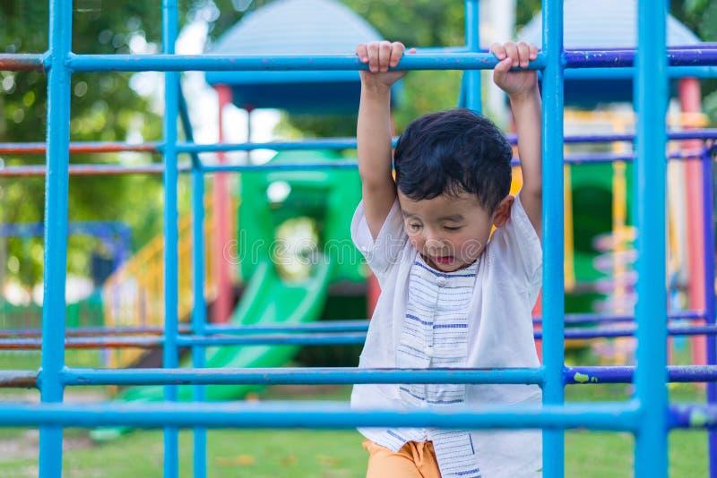 Coup asiatique de garçon la barre en métal au terrain de jeu extérieur photos libres de droits