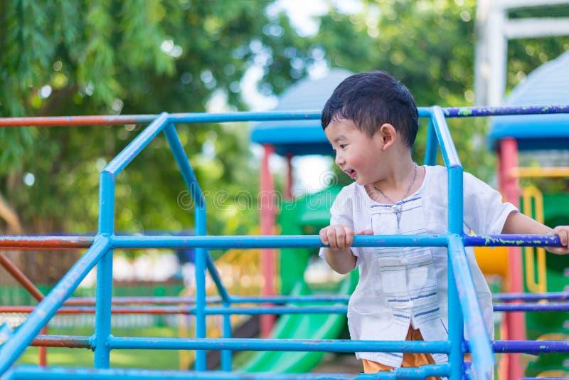 Coup asiatique de garçon la barre en métal au terrain de jeu extérieur images stock