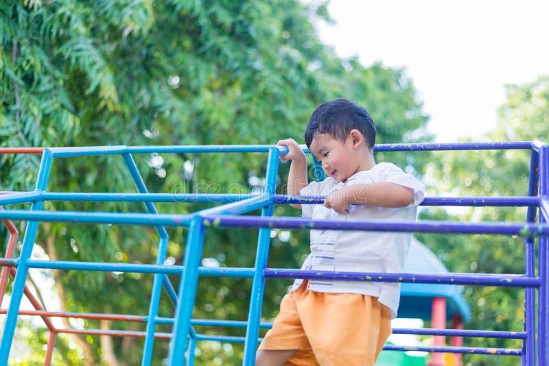 Coup asiatique de garçon la barre en métal au terrain de jeu extérieur image stock