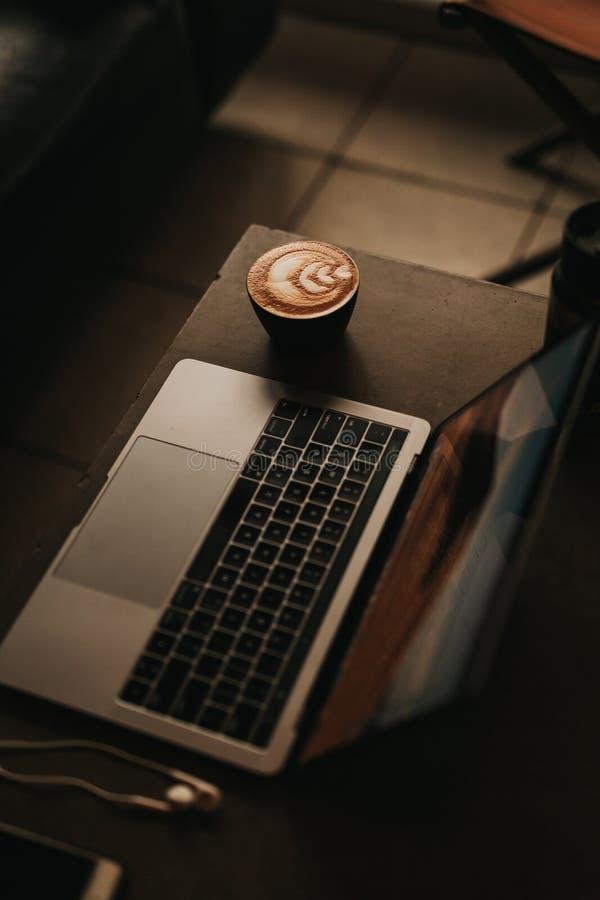 Coup courbe d'un ordinateur portable avec un cappuccino admirablement fait avec l'art de fleur du côté photo libre de droits