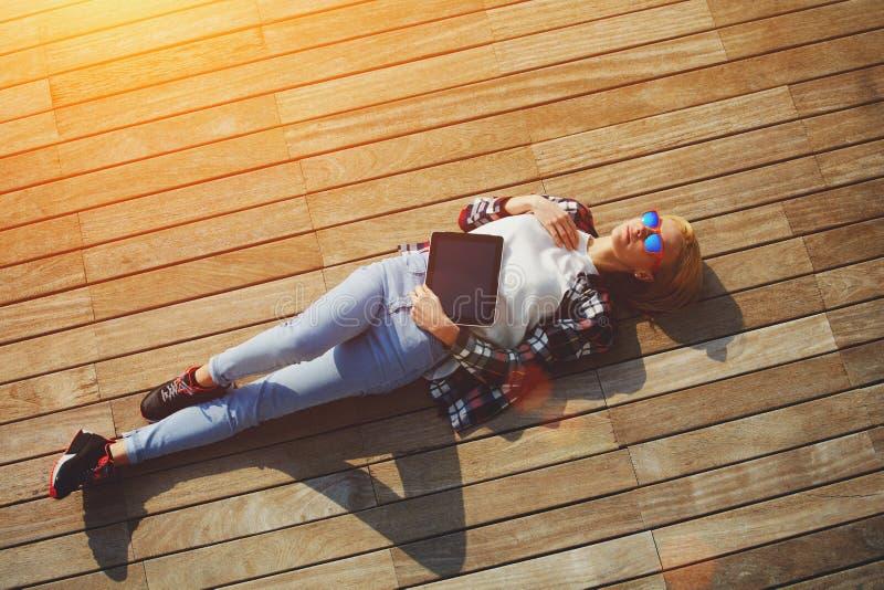 Coup courbe de jeune femme insouciante en verres d'été se trouvant sur la jetée en bois au soleil images stock